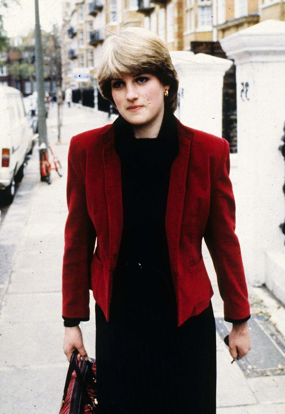 <p>In a red velvet blazer, pinstripe skirt, and black cowl-neck jumper, with small gold hoop earrings on the streets of London. </p>