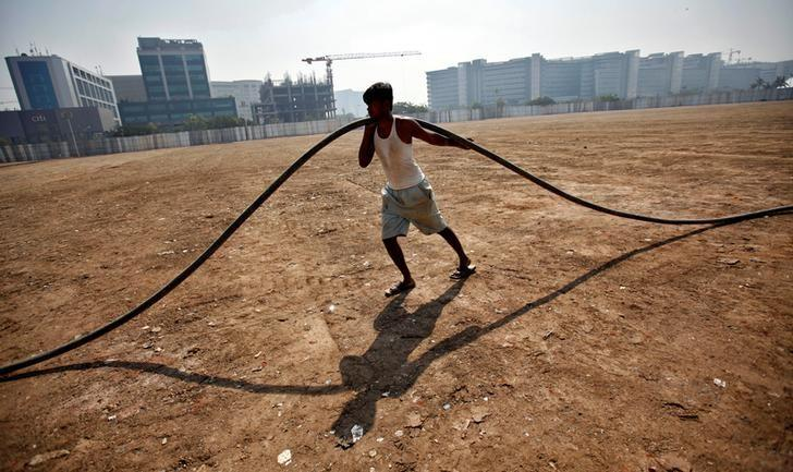 A labourer pulls an underground cable at a construction site of a commercial complex in Mumbai