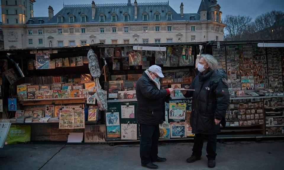 Fancis, who celebrates working as a Bouquiniste for 40 years this year (right), talks to a customer at his book stall on the Seine on 3 January 2021.