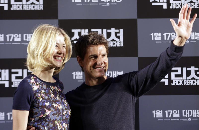 """U.S. actor Tom Cruise, right, and British actress Rosamund Pike pose for photographers during a news conference to promote their film """"Jack Reacher"""" in Seoul, South Korea, Thursday, Jan. 10, 2013. Even though he turned 50 last summer and has been a Hollywood star for three decades, Tom Cruise says he still has fun making movies. (AP Photo/Lee Jin-man)"""