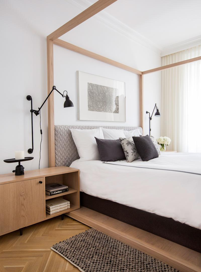 """A minimalist custom-designed four-poster bed anchors the master bedroom. """"It's really seamless woodwork inspired by Japanese traditions; there's no hardware,"""" says Grehl of the piece, which was built by A.B. Hornbake (as were the matching bedside tables). The adjustable reading lamps, designed in the '20s by Bernard-Albin Gras, are from Design Within Reach. To add coziness, Grehl picked an upholstered headboard covered in Patricia Urquiola's """"Big Braid"""" fabric, and a textured wool carpet from Bludot."""