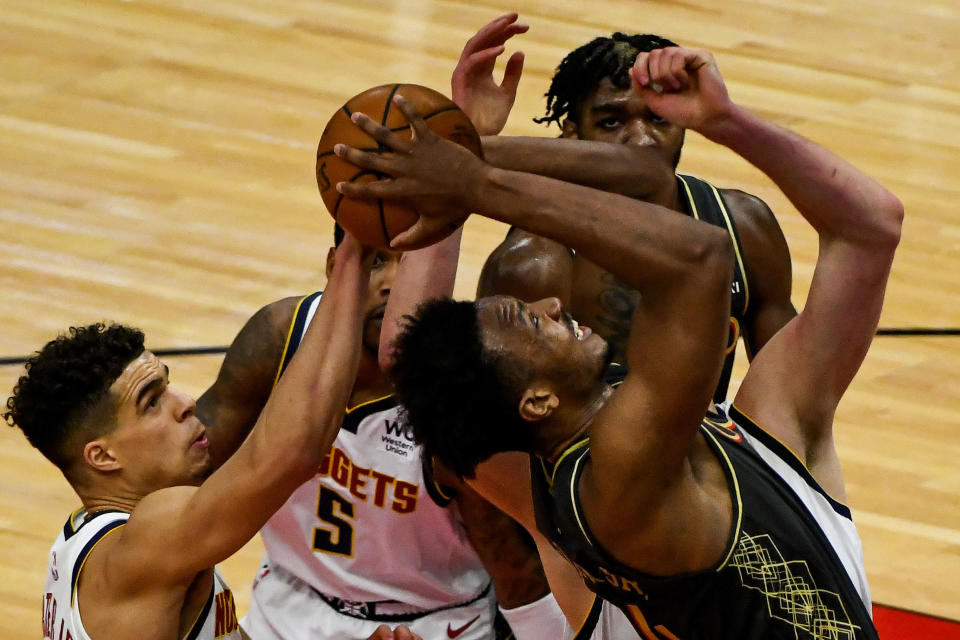 Chicago Bulls center Wendell Carter Jr., right, fights for the ball with Denver Nuggets forward Michael Porter Jr., left, forward Will Barton (5) and center Nikola Jokic, back, during the first half of an NBA basketball game Monday, March 1, 2021, in Chicago. (AP Photo/Matt Marton)