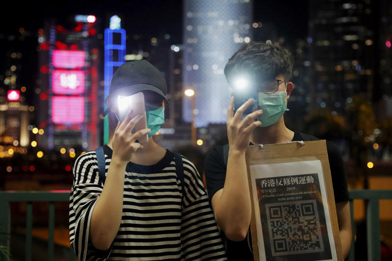 Demonstrators hold up their smartphones as they gather during a protest in Hong Kong, Friday, Aug. 23, 2019. Supporters of Hong Kong's pro-democracy movement created human chains on both sides of the city's harbor Friday, inspired by a historic protest 30 years ago in the Baltic states against Soviet control. (AP Photo/Kin Cheung)
