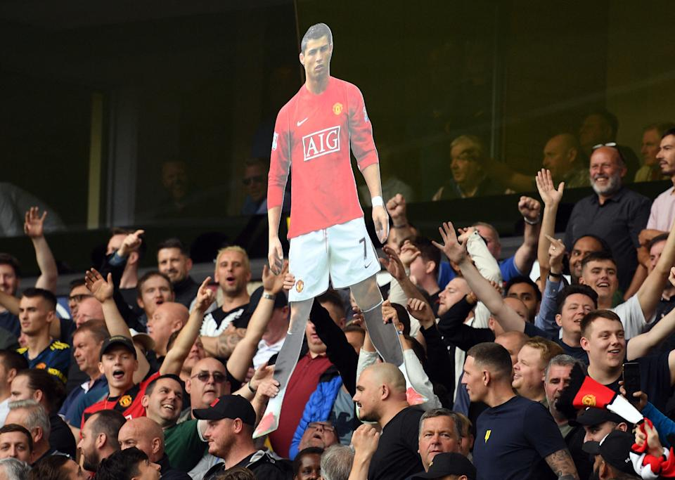 A cardboard cut out of new signing Cristiano Ronaldo is held by Manchester United supporters during the English Premier League football match between Wolves and Manchester United.