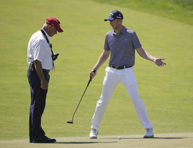 Daniel Berger talks to an official on the first green during the third round of the U.S. Open Golf Championship, Saturday, June 16, 2018, in Southampton, N.Y. (AP Photo/Seth Wenig)