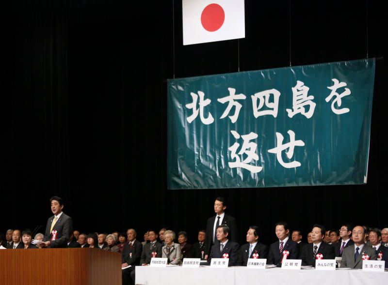 """Japanese Prime Minister Shinzo Abe, left, delivers his speech during a national rally marking the Northern Territories Day in Tokyo Thursday, Feb. 7, 2013. Japan reiterated its demand to Russia the return of the four-island chain, known as the Northern Territories in Japan and the Kuril islands in Russia. The banner on the wall reads: """"Return the four northern islands."""" (AP Photo/Koji Sasahara)"""