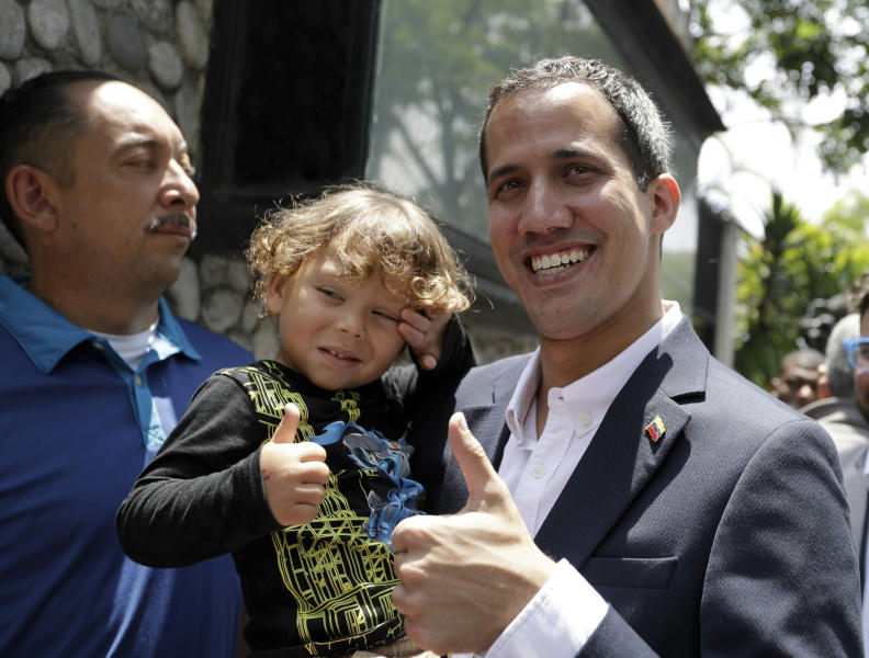 "Opposition leader Juan Guaido, who has declared himself interim president of the country, flashes a thumbs up as he poses for a photo with a toddler, in Caracas, Venezuela, Thursday, March 21, 2019. Guaido says the Venezuelan government is weak and doesn't ""dare"" to detain him. Guaido spoke Thursday after intelligence agents staged an overnight raid and detained Roberto Marrero, his key aide. (AP Photo/Natacha Pisarenko)"