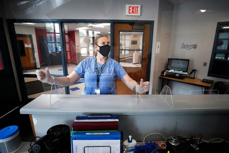 Des Moines Public Schools employee Sarah Holland installs a plexiglass shield in the office at Oak Park Elementary School on July 30, 2020, in Des Moines, Iowa. (Photo: ASSOCIATED PRESS)