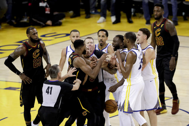 An official tries to separate Tristan Thompson and Draymond Green during overtime of Game 1 of the NBA Finals. (AP Photo/Marcio Jose Sanchez)