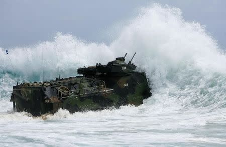 A U.S. Marine Corps amphibious assault vehicle charges through the surf during RIMPAC in Hawaii