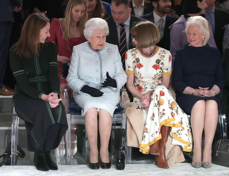 Britain's Queen Elizabeth II, accompanied by Chief Executive of the British Fashion Council (BFC), Caroline Rush (L), British-American journalist and editor, Anna Wintour (2R) and royal dressmaker Angela Kelly, views British designer Richard Quinn's runway show before presenting him with the inaugural Queen Elizabeth II Award for British Design, during her visit to London Fashion Week's BFC Show Space in central London on February 20, 2018.