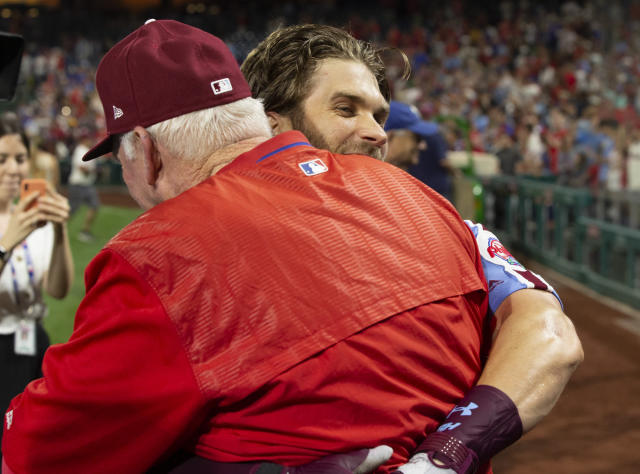 Philadelphia Phillies' Bryce Harper, right, gives hitting coach Charlie Manuel a hug after his grand slam ended the team's baseball game against the Chicago Cubs, Thursday, Aug. 15, 2019, in Philadelphia. The Phillies won 7-5. (AP Photo/Chris Szagola)