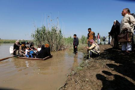 Displaced Iraqis from Mosul cross the Tigris by boat as flooding after days of rainfall has closed the city's bridges, at the village of Thibaniya