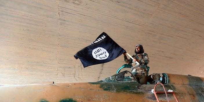 Islamic State fighter (ISIS; ISIL) waving a flag while standing on captured government fighter jet in Raqqa, Syria, 2015.