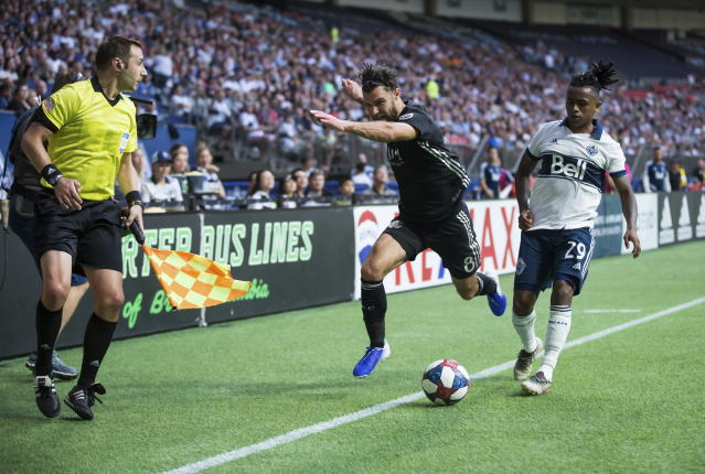 Sporting Kansas City's Graham Zusi (8) stumbles after after colliding with Vancouver Whitecaps' Yordy Reyna (29) during the first half of an MLS soccer match Saturday, July 13, 2019, in Vancouver, British Columbia. (Darryl Dyck/The Canadian Press via AP)