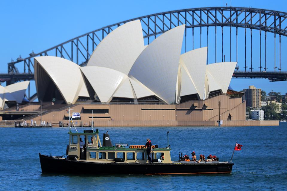 Dancers from Handa Opera's production of La Traviata sail past the Sydney Opera House as they arrive by boat for a rehearsal at an over-water stage at Mrs Macquaries Chair, ahead of the launch of new shows later this month in Sydney on March 15, 2021. (Photo by Steven Saphore / AFP) (Photo by STEVEN SAPHORE/AFP via Getty Images)