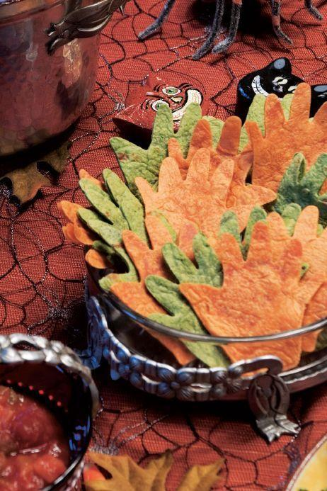"""<p>Use a cookie cutter to turn orange and green tortillas into spooky-looking hands. Serve them alongside your favorite salsa and your party guests are sure to be impressed.</p><p><em><a href=""""https://www.womansday.com/food-recipes/food-drinks/a28860345/tortilla-hands-and-salsa-recipe/"""" rel=""""nofollow noopener"""" target=""""_blank"""" data-ylk=""""slk:Get the Tortilla Hands and Salsa recipe."""" class=""""link rapid-noclick-resp"""">Get the Tortilla Hands and Salsa recipe.</a></em> </p>"""