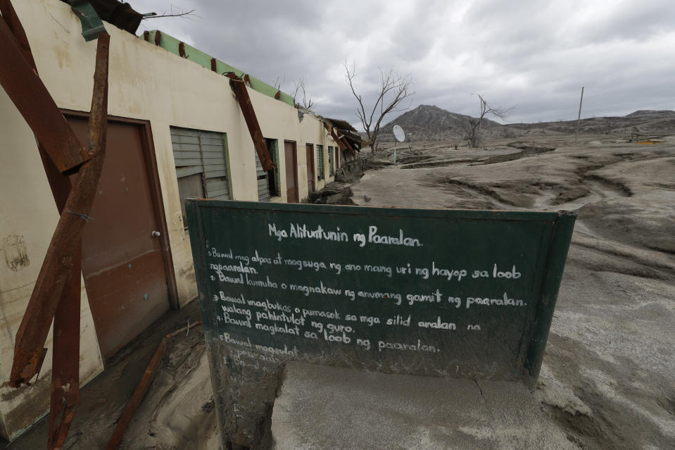 A sign stands beside the remains of the Alas-as elementary school at the Taal volcano almost a year after it erupted on Sunday, Jan. 10, 2021 in Batangas province, Philippines. A popular tourist destination just south of Manila because of its picturesque setting in the middle of a lake, Taal erupted on Jan. 12, 2020. The eruption displaced thousands of villagers living near the area and delivered an early crisis this year for one of the world's most disaster-prone nations a couple of months before the COVID-19 pandemic broke in the country. (AP Photo/Aaron Favila)