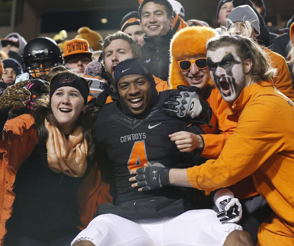 Oklahoma State's Justin Gilbert (4) celebrates with fans following victory over Baylor in an NCAA college football game in Stillwater, Okla., Saturday, Nov. 23, 2013. Oklahoma State won 49-17. (AP Photo/Sue Ogrocki)