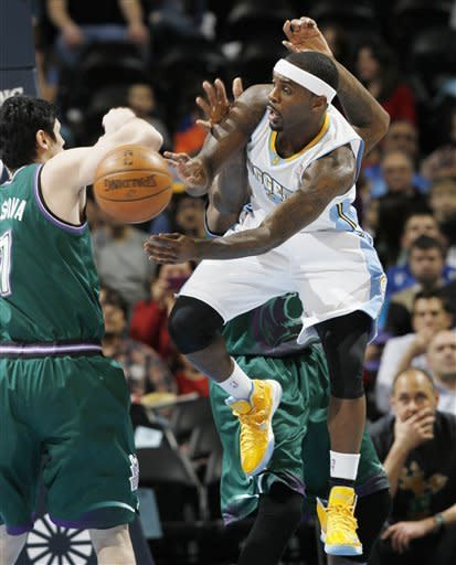 Denver Nuggets guard Ty Lawson, front, loses control of the ball as he tries to drive the lane past Milwaukee Bucks forward Ersan Ilyasova, left, of Turkey, and center Larry Sanders in the first quarter of an NBA basketball game in Denver on Tuesday, Feb. 5, 2013. (AP Photo/David Zalubowski)