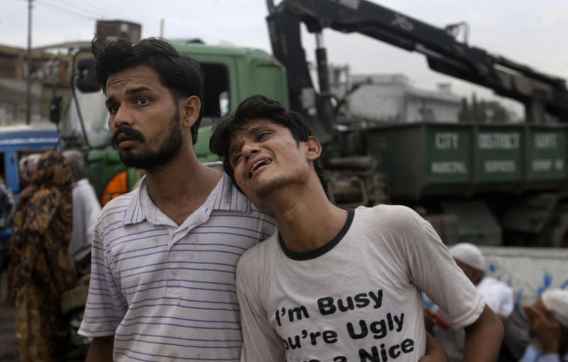 A Pakistani man comforts to another who weeps at the site of burnt garment factory in Karachi, Pakistan on Wednesday, Sept. 12, 2012. Pakistani officials say the death toll from devastating factory fires that broke out in two major cities has risen to 128. Hospital official Tariq Kaleem said the fire at a garment factory in the southern Pakistani city of Karachi killed 103 people. A blaze at a shoe factory in the eastern city of Lahore killed 25 people. (AP Photo/Fareed Khan)