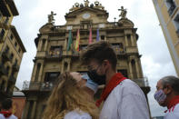 Aitana Agudo and Iraitz Iriarte, right, wearing face protection, kiss in front of the City Hall in Pamplona, northern Spain, Tuesday July 6, 2021, on the day the ''txupinazo'' would usually take place to start the famous San Fermin festival, which was canceled for another year due to the COVID-19 pandemic. (AP Photo/Alvaro Barrientos)