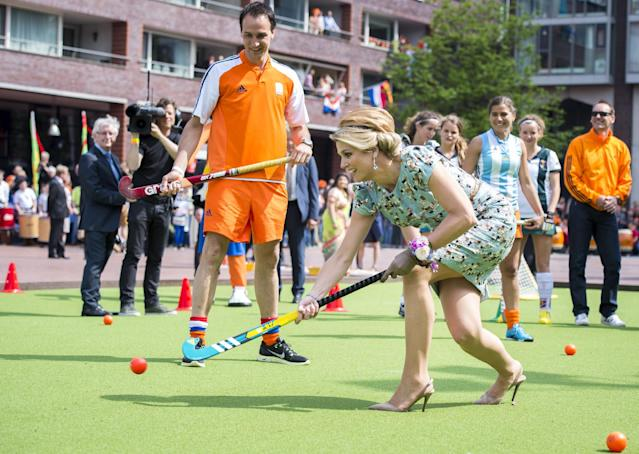Queen Maxima plays hockey during festivities marking King's Day in Amstelveen, near Amsterdam, Netherlands, Saturday, April 26, 2014. The Dutch celebrate the first ever King's Day, a national holiday held in honor of the newly installed monarch, King Willem Alexander. King's Day replaces the traditional Queen's Day. (AP Photo/Frank van Beek, Pool)
