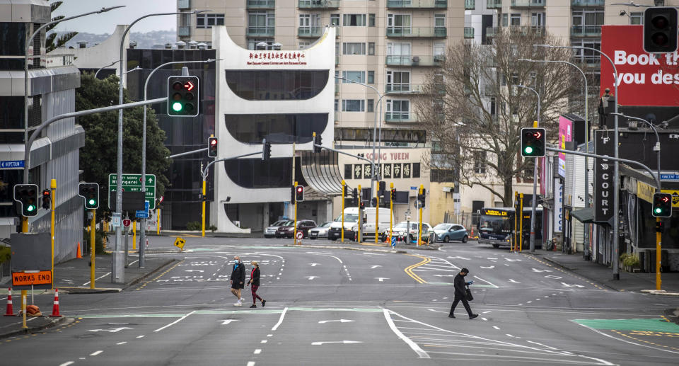 People cross nearly empty streets in the central business district of Auckland, New Zealand, on August 27, 2021.
