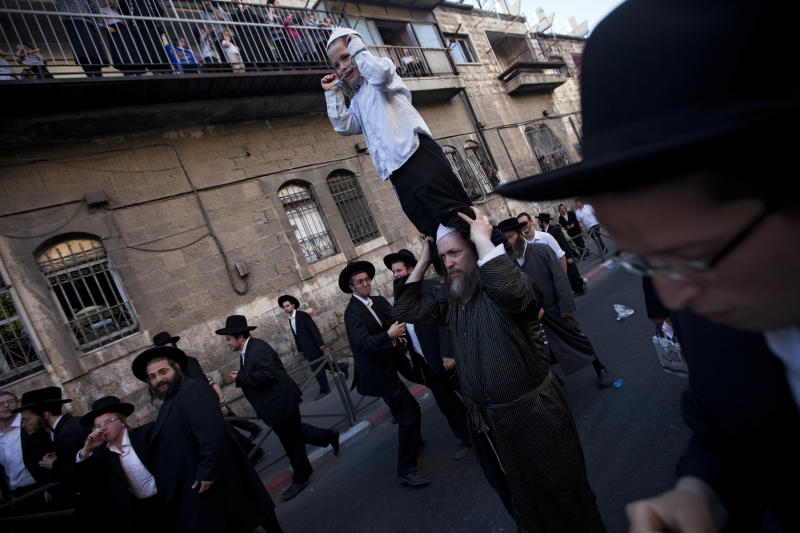 An Ultra Orthodox Jewish man caries a Handcuffed boy  during a protest against attempts to draft members of the cloistered community into the Israeli military, in an ultra Orthodox neighborhood in Jerusalem, Israel, Monday, July 16, 2012. Thousands of ultra-Orthodox Jews, including hundreds of children, are protesting against attempts to draft members of the cloistered community into the Israeli military. The government is currently trying to find a formula to obligate ultra-Orthodox Jews to serve in the military before a court-determined Aug. 1 deadline. ? The current law largely exempts the community from military service. That infuriates many Israelis, since almost all are required to serve. Israel's Supreme Court ruled the law must be revised. (AP Photo/Oded Balilty)