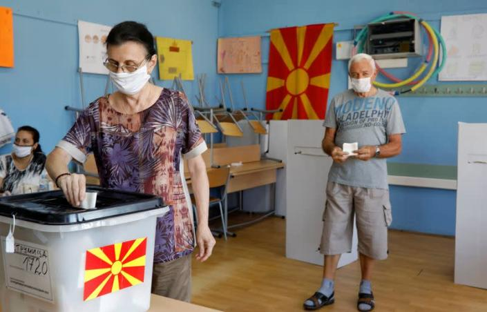 A woman wearing a face mask casts her ballot at a polling station during the general election, in Strumica