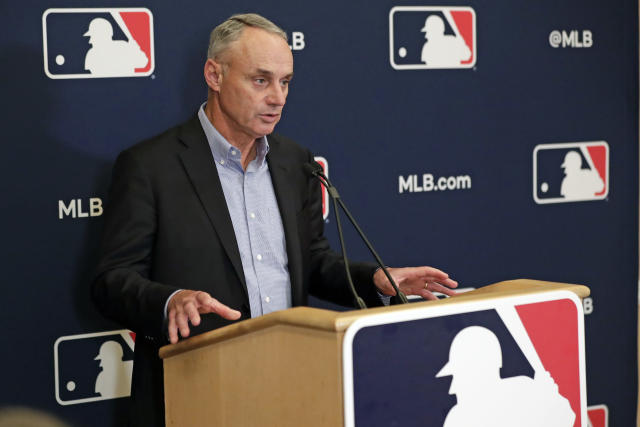"""FILE - In this Feb. 6, 2020, file photo, Baseball Commissioner Rob Manfred answers questions at a press conference during baseball owners meetings in Orlando, Fla. Manfred tells The Associated Press that the commissioner's office, teams and the players' association """"owe it to our fans to be better than we've been the last three months."""" (AP Photo/John Raoux, File)"""