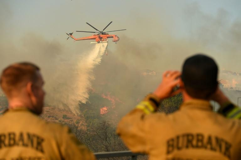 Firefighters watch a helicopter drop water on a burning hillside in Porter Ranch, California on October 11, 2019 (AFP Photo/Josh Edelson)