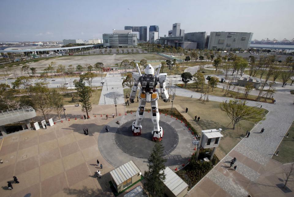 People walk around a full-size model of Japan's popular robot animation character Gundam standing in front of a new shopping mall in Tokyo's Odaiba waterfront area Tuesday, April 17, 2012. The 18-meter (60-foot)-tall Gundam greets shoppers at Diver City Tokyo Plaza which opens on Thursday. (AP Photo/Koji Sasahara)