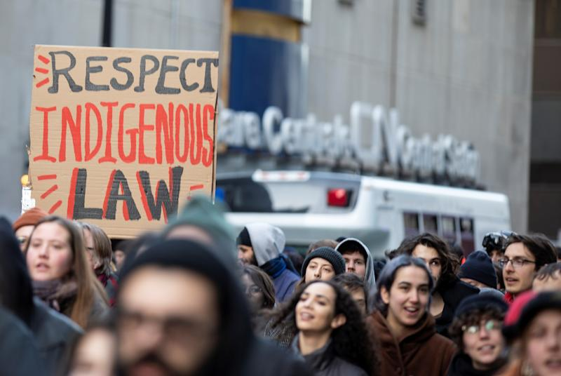 Supporters of the indigenous Wet'suwet'en Nation's hereditary chiefs pass by CN Rail as they march as part of protests against British Columbia's Coastal GasLink pipeline, in Montreal, Quebec, Canada February 25, 2020. REUTERS/Christinne Muschi