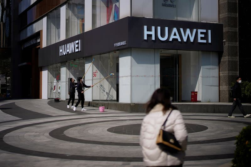 People wearing face masks are seen at a Huawei shop on a street as the country is hit by an outbreak of the novel coronavirus