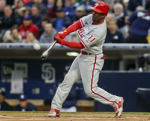 Philadelphia Phillies' Jimmy Rollins lofts a sacrifice fly to right field to drive in Juan Pierre from third base in the first inning of a baseball game against the San Diego Padres Thursday, April 19, 2012, in San Diego. (AP Photo/Lenny Ignelzi)