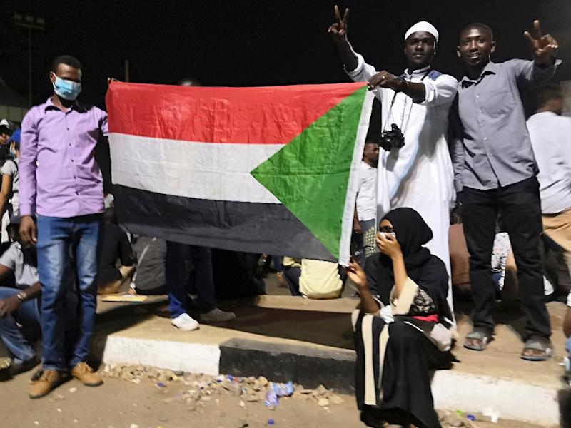 Protesters hold the national flag, after Sudan's police on Tuesday ordered officers to avoid intervening against protesters (AFP Photo/-)