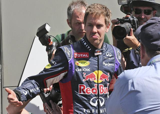 Red Bull driver Sebastian Vettel of Germany holds his arms out as he walks around the paddock ahead of the Australian Formula One Grand Prix at Albert Park in Melbourne, Australia, Thursday, March 13, 2014. (AP Photo/Rob Griffith)
