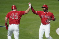 Los Angeles Angels' Justin Upton, right, is high-fived by Mike Trout after they both scored on single from Jared Walsh during the fourth inning of a baseball game against the Minnesota Twins Friday, April 16, 2021, in Anaheim, Calif. (AP Photo/Marcio Jose Sanchez)