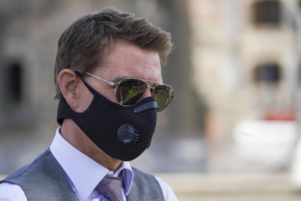 Actor Tom Cruise wears a face mask to prevent the spread of COVID-19 as he greets fans during a break from shooting Mission Impossible 7, along Rome's Fori Imperiali avenue, Tuesday, Oct. 13, 2020. (AP Photo/Andrew Medichini)