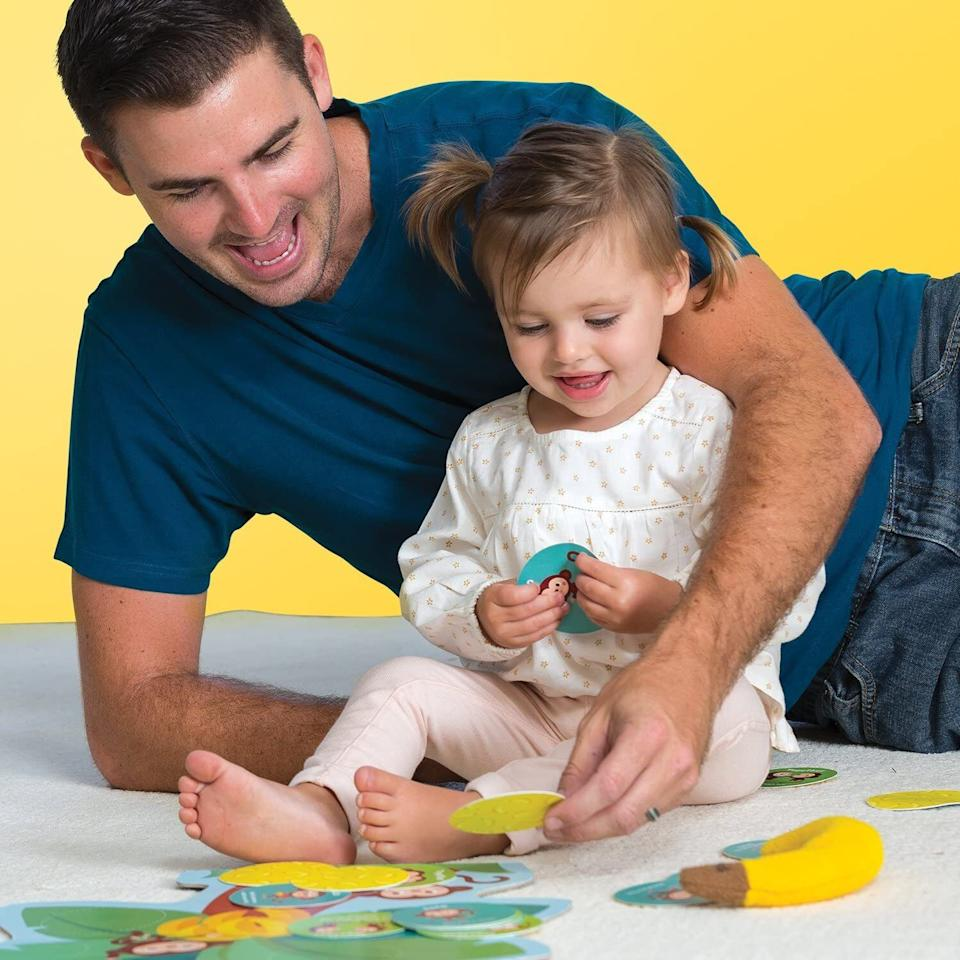 """With a beanbag banana that involves simple skills like balancing, hopping and marching (as well as high fives and hugs), this game encourages motor skill development, coordination, understanding spatial concepts and, most importantly, fun with the family.<br /><br /><strong>Promising review:</strong>""""I love, love, love board games and my kiddo is a little young for them so I have been looking for things that he might be interested in and found this game. He isn't quite two yet, but we have tried to play a couple of times and he likes it!<strong>There isn't a winner or loser here, there aren't really a lot of rules, it's just a fun structured play with your kiddo and helps them learn how to follow directions and make choices.</strong>It's so much fun and I know that he will be able to understand it better in the coming months and enjoy it even more!"""" —<a href=""""https://amzn.to/32Am4YS"""" target=""""_blank"""" rel=""""noopener noreferrer"""">Shannizzle</a><br /><strong><br />Get it from Amazon for<a href=""""https://amzn.to/3atx3HF"""" target=""""_blank"""" rel=""""noopener noreferrer"""">$17.99</a>.</strong>"""