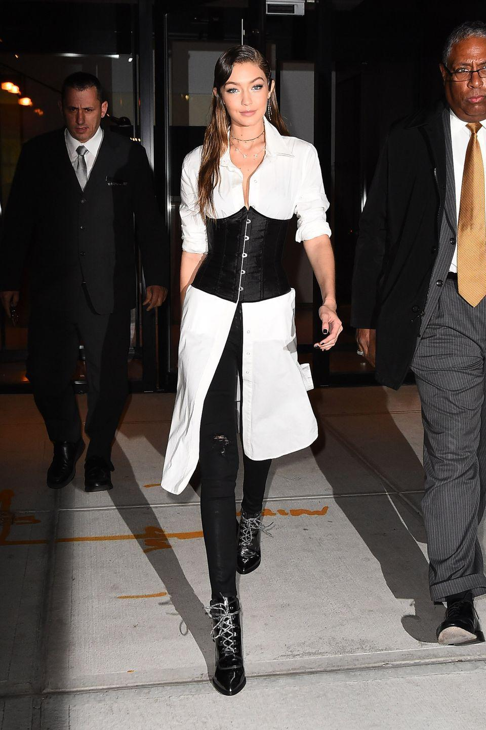 """<p>In a black satin corset over a white button-down shirtdress, black ripped skinny jeans and her <a href=""""https://www.harpersbazaar.com/fashion/models/news/a18391/gigi-hadid-stuart-weitzman-boot/"""" rel=""""nofollow noopener"""" target=""""_blank"""" data-ylk=""""slk:Gigi boot"""" class=""""link rapid-noclick-resp"""">Gigi boot</a>, which she designed for Stuart Weitzman, while out in NYC. </p>"""