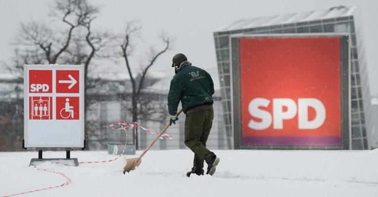 File picture shows a man sweeping snow from a street before a special federal party conference of Germany's Social Democratic Party (SPD) last year in Hanover. The opposition SPD mark its 150th birthday Thursday, with French President Francois Hollande as the only foreign speaker and conservative Chancellor Angela Merkel in the audience
