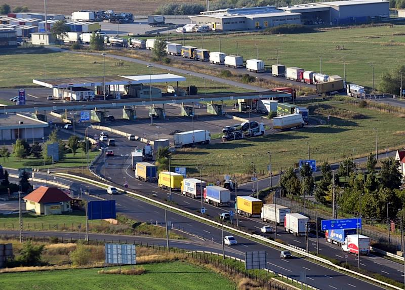 Vans and trucks wait to be checked by Austrian border officials on the M1 highway in front of the former border station of Hegyeshalom, on August 31, 2015 (AFP Photo/Attila Kisbenedek)