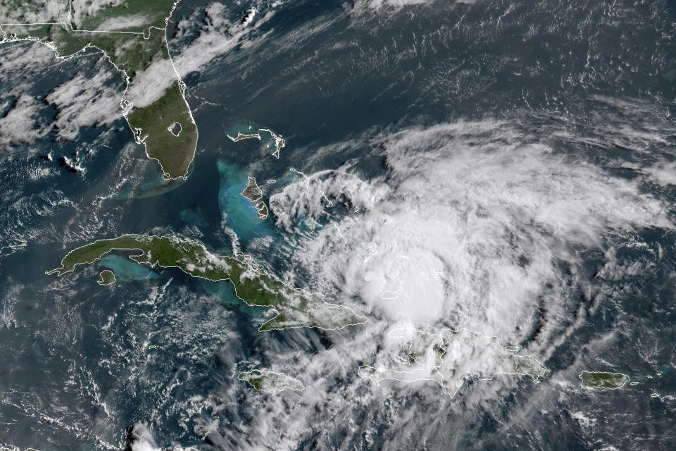 In this GOES-16 satellite image taken Friday, July 31, 2020, at 8:40 a.m. EDT., and provided by NOAA, Hurricane Isaias churns in the Caribbean. Hurricane Isaias kept on a path early Friday toward the U.S. East Coast as it approached the Bahamas, parts of which are still recovering from the devastation of last year's Hurricane Dorian. (NOAA via AP)