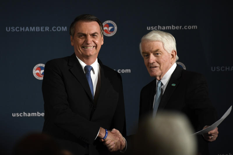 Brazilian President Jair Bolsonaro, left, shakes hands with Chamber of Commerce President and Chief Executive Officer Thomas Donohue, right, as he arrives on stage before speaking at the Chamber of Commerce in Washington, Monday, March 18, 2019. (AP Photo/Susan Walsh)