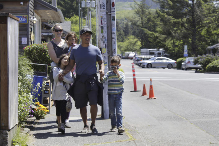 In this Thursday, May 28, 2020, photo, tourists Tuan Nguyen and his wife, Sarah Nguyen, walk with their children, twins Lukas and Lauren, 7, and Alyssa, 4, as they walk through downtown in Cannon Beach, Ore. The Nguyens were visiting from the Portland, Ore., suburbs but elected to stay in their RV instead of a hotel to feel safer from the coronavirus. (AP Photo/Gillian Flaccus)