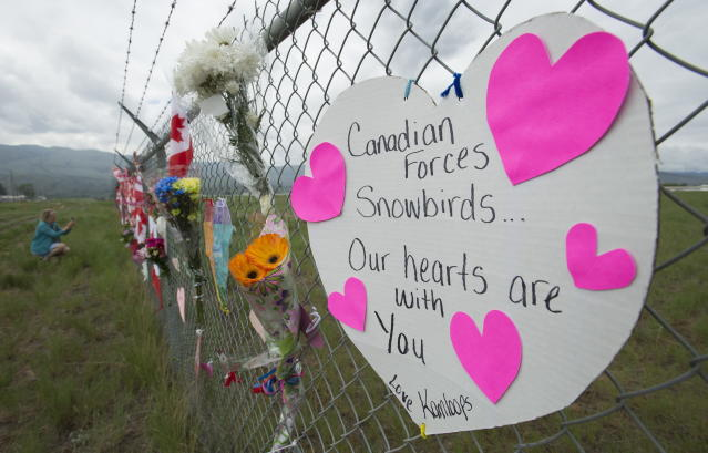 Signs are attached to the fence of the Kamloops airport to show respect for the Canadian Forces Snowbirds in Kamloops, British Columbia, Monday, May 18, 2020. Capt. Jenn Casey died Sunday after the Snowbirds jet she was in crashed shortly after takeoff. The pilot of the aircraft is in hospital with serious injuries. (Jonathan Hayward/The Canadian Press via AP)