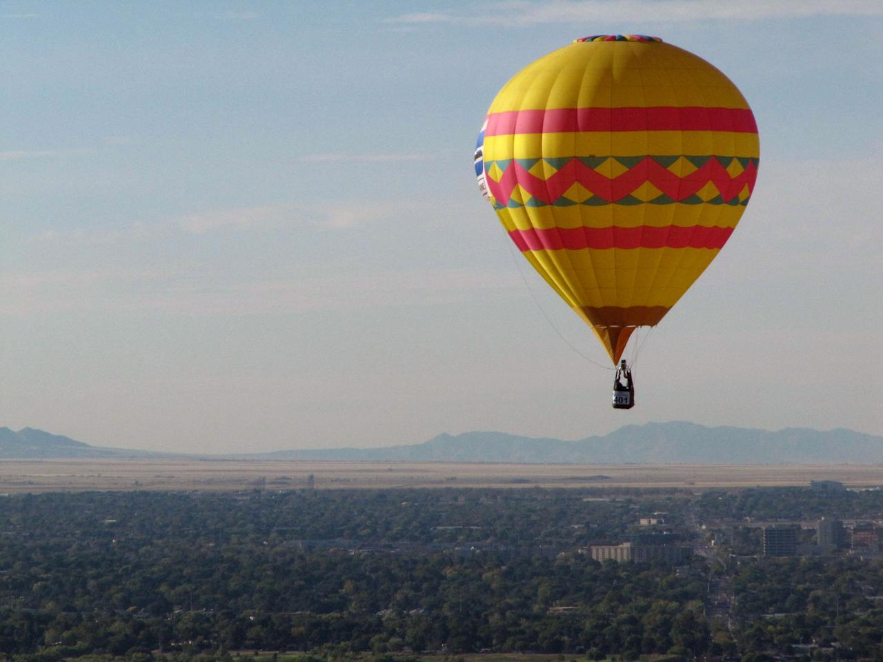 A hot air balloon floats over Albuquerque, N.M., on Tuesday, Oct. 5, 2010. The annual Albuquerque International Balloon Fiesta has attracted about 500 balloons and thousands of spectators.