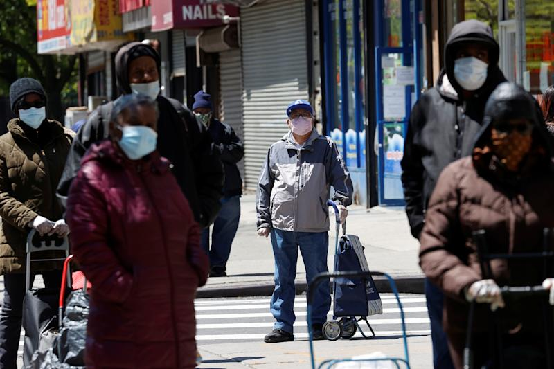 People wearing protective face masks wait in line at a free food distribution for people in need, outside the West Harlem Group Assistance in Manhattan, during the outbreak of the coronavirus disease (COVID-19) in New York city, New York, U.S., May 12, 2020. REUTERS/Mike Segar - RC25NG9N38MX